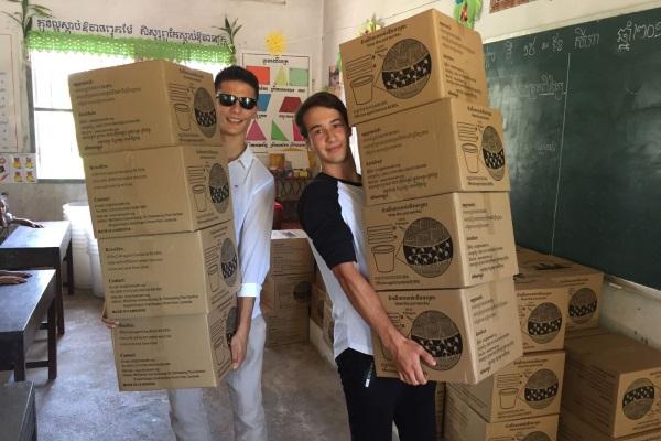 I Due Studenti In Cambogia Con Le Scatole Contenenti I Filtri Per Potabilizzare L'acqua